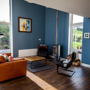 Example of a trendy open concept dark wood floor living room design in Cork with blue walls, a wood stove and a tv stand