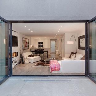 Ispirazione per un soggiorno design di medie dimensioni e stile loft con sala formale, pareti bianche, pavimento in legno massello medio, camino sospeso, cornice del camino in intonaco, parete attrezzata e pavimento marrone