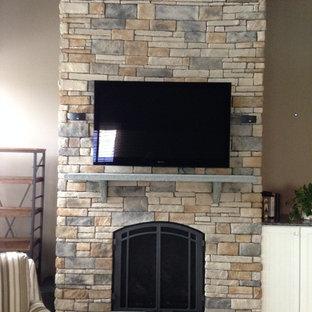 他の地域の中サイズのおしゃれな独立型リビング (グレーの壁、カーペット敷き、標準型暖炉、石材の暖炉まわり、壁掛け型テレビ) の写真