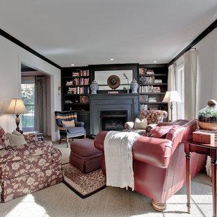 Immagine di un piccolo soggiorno classico chiuso con libreria, pareti beige, moquette, camino classico, cornice del camino in legno e nessuna TV