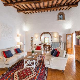 Ejemplo de salón abierto, mediterráneo, grande, con paredes blancas, suelo de madera clara y suelo marrón