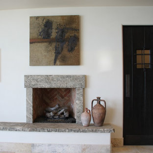 Ispirazione per un soggiorno mediterraneo di medie dimensioni e chiuso con sala formale, pareti bianche, pavimento in travertino, camino classico e cornice del camino in pietra