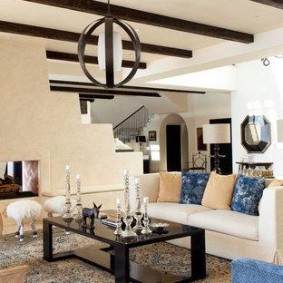 Esempio di un soggiorno mediterraneo chiuso e di medie dimensioni con sala formale, pareti beige, camino bifacciale, cornice del camino in intonaco e pavimento in travertino