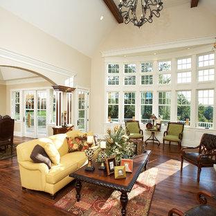 Elegant dark wood floor and brown floor living room photo in Other with beige walls