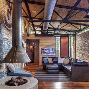Idee per un piccolo soggiorno industriale aperto con parquet chiaro, camino sospeso, cornice del camino in cemento e TV a parete