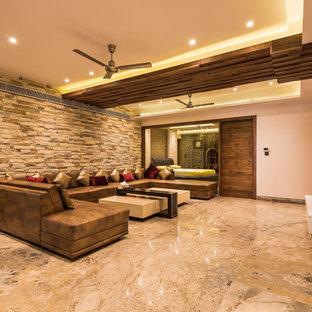 Ejemplo de salón para visitas cerrado, actual, grande, con suelo de mármol, televisor colgado en la pared y suelo marrón