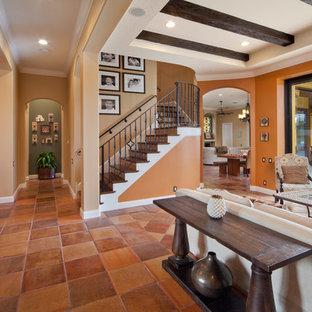 Immagine di un grande soggiorno mediterraneo aperto con sala formale, pareti arancioni, pavimento in terracotta, camino classico, cornice del camino piastrellata e nessuna TV
