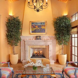 Exemple d'un salon méditerranéen avec un mur jaune, une cheminée standard et un manteau de cheminée en pierre.