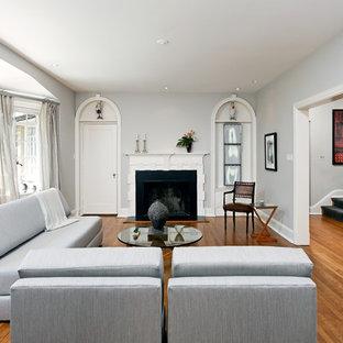 Inredning av ett klassiskt vardagsrum, med en standard öppen spis, grå väggar och brunt golv