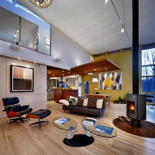 Imagen de salón abierto, actual, con paredes amarillas y estufa de leña