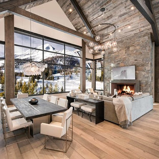 Example of a mountain style open concept medium tone wood floor and brown floor living room design in Other with gray walls and a standard fireplace