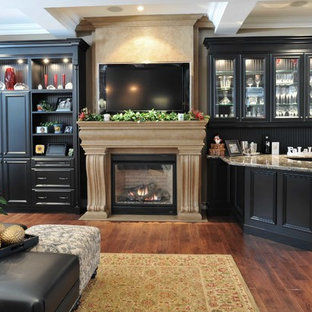 Photo of a large traditional enclosed living room in Other with a home bar, white walls, medium hardwood floors, a standard fireplace, a stone fireplace surround, a built-in media wall and brown floor.