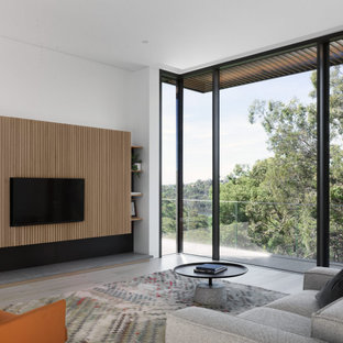 Inspiration for an expansive modern open concept living room in Sydney with white walls, light hardwood floors, a wall-mounted tv and beige floor.