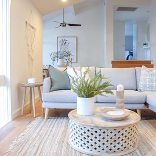 Photo of a beach style formal open concept living room in Sydney with white walls, medium hardwood floors and beige floor.