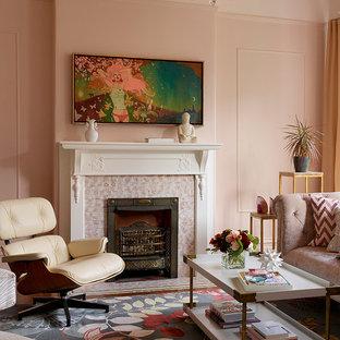 Diseño de salón cerrado, contemporáneo, pequeño, sin televisor, con paredes rosas, suelo de madera en tonos medios, chimenea tradicional y marco de chimenea de baldosas y/o azulejos