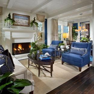 オレンジカウンティの中サイズのトラディショナルスタイルのおしゃれなLDK (フォーマル、青い壁、濃色無垢フローリング、標準型暖炉、テレビなし、漆喰の暖炉まわり、茶色い床) の写真