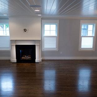プロビデンスの中サイズのビーチスタイルのおしゃれなリビング (グレーの壁、濃色無垢フローリング、木材の暖炉まわり、標準型暖炉) の写真