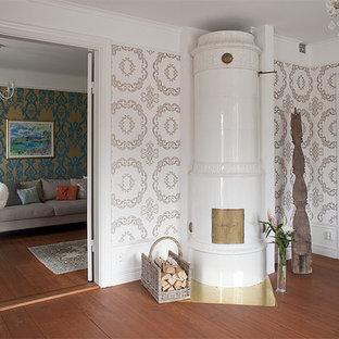 ストックホルムの中サイズのカントリー風おしゃれな独立型リビング (マルチカラーの壁、濃色無垢フローリング、コーナー設置型暖炉、テレビなし) の写真