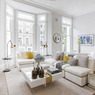 Esempio di un soggiorno tradizionale di medie dimensioni e aperto con pareti bianche, TV a parete, pavimento beige e parquet chiaro