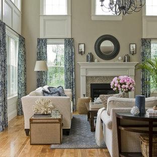 Immagine di un grande soggiorno classico con pareti beige, camino classico, nessuna TV e pavimento arancione
