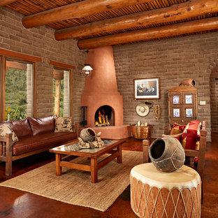 フェニックスの広いサンタフェスタイルのおしゃれな独立型リビング (フォーマル、コーナー設置型暖炉、漆喰の暖炉まわり、茶色い壁、コンクリートの床、テレビなし) の写真