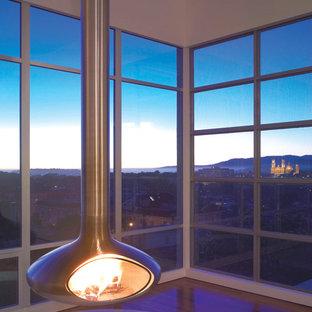 Immagine di un piccolo soggiorno moderno aperto con pareti bianche, parquet scuro, camino sospeso e cornice del camino in metallo