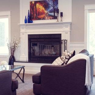 Foto di un soggiorno american style aperto con pareti grigie, moquette, camino classico, cornice del camino in legno e TV a parete