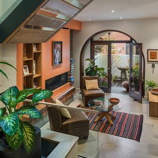 Ejemplo de salón abierto, actual, con parades naranjas, suelo de baldosas de porcelana, chimenea lineal y suelo gris