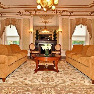 Cette image montre un grand salon victorien fermé avec une salle de réception, un mur vert, un sol en bois foncé, un manteau de cheminée en pierre, aucun téléviseur, une cheminée standard et un sol marron.