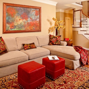 This is an example of a mid-sized traditional open concept living room in Houston with beige walls, medium hardwood floors, a concealed tv, no fireplace and brown floor.