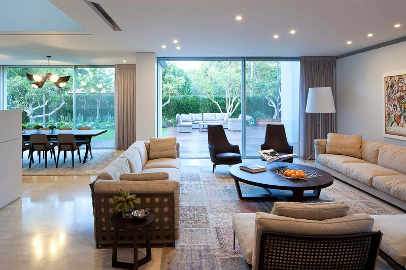 contemporary living room by Domb architects, white couches surrounding black round coffee table.