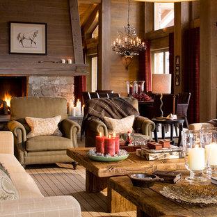 Idée de décoration pour un grand salon chalet ouvert avec une salle de réception, un mur marron, un sol en bois brun, une cheminée standard et un manteau de cheminée en pierre.