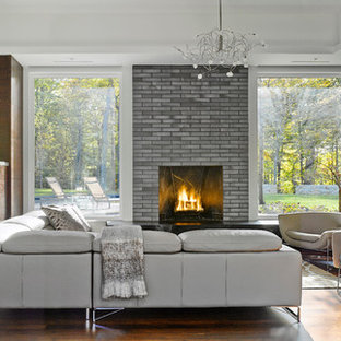 Photo of a large contemporary formal open concept living room in Burlington with a standard fireplace, a brick fireplace surround, a wall-mounted tv, laminate floors and multi-coloured walls.