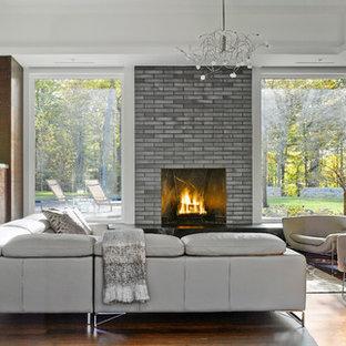 バーリントンの広いコンテンポラリースタイルのおしゃれなLDK (フォーマル、標準型暖炉、レンガの暖炉まわり、壁掛け型テレビ、ラミネートの床、マルチカラーの壁) の写真