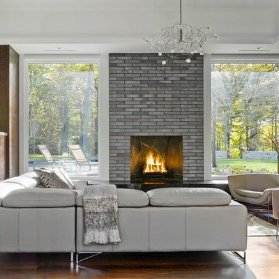 Large trendy formal and open concept laminate floor living room photo in Burlington with a standard fireplace, a brick fireplace, a wall-mounted tv and multicolored walls