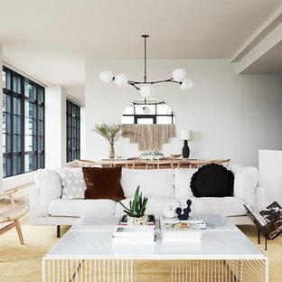 Inredning av ett minimalistiskt allrum med öppen planlösning, med ett finrum, vita väggar och ljust trägolv