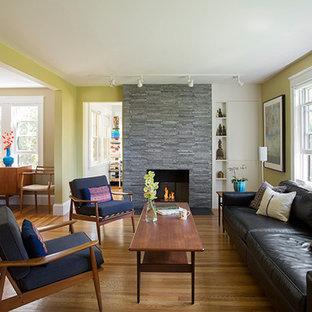 Imagen de salón abierto, retro, pequeño, con paredes verdes, suelo de madera en tonos medios, chimenea tradicional y marco de chimenea de piedra