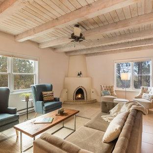 他の地域の中サイズのサンタフェスタイルのおしゃれな独立型リビング (白い壁、トラバーチンの床、コーナー設置型暖炉、漆喰の暖炉まわり、テレビなし、ベージュの床) の写真