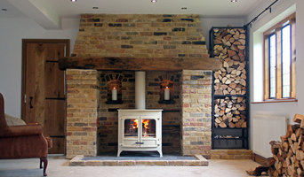Charnwood island 3b wood boiler stove with reclaimed brick and oak fireplace