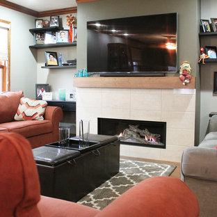 他の地域の広いサンタフェスタイルのおしゃれな独立型リビング (フォーマル、緑の壁、無垢フローリング、標準型暖炉、タイルの暖炉まわり、壁掛け型テレビ) の写真