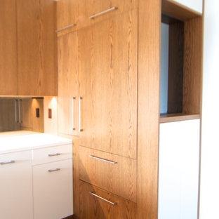Foto di un piccolo soggiorno minimal stile loft con libreria, pareti gialle, parquet scuro e TV nascosta