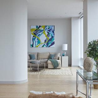 Example of a trendy light wood floor and beige floor living room design in New York with gray walls