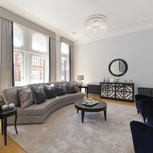 Large classic formal enclosed living room in London with grey walls, light hardwood flooring and beige floors.