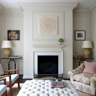 Design ideas for a medium sized classic living room in London with white walls, painted wood flooring, a standard fireplace, a stone fireplace surround and brown floors.