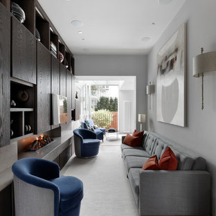 This is an example of a medium sized contemporary living room in London with white walls, a concrete fireplace surround, a wall mounted tv and beige floors.