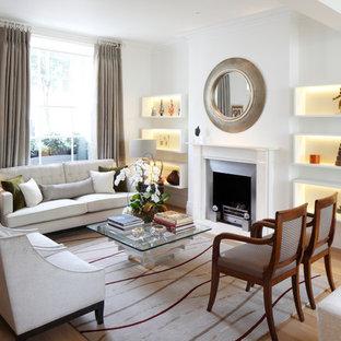 Idée de décoration pour un salon tradition avec une salle de réception, un mur blanc, un sol en bois clair, une cheminée standard et un manteau de cheminée en métal.