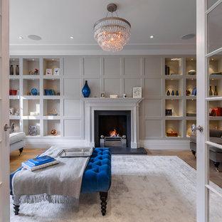 ロンドンの広いトランジショナルスタイルのおしゃれな独立型リビング (フォーマル、グレーの壁、無垢フローリング、テレビなし、標準型暖炉、茶色い床) の写真
