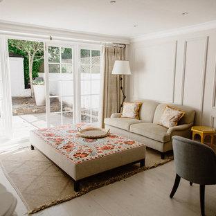 ロンドンの中サイズのエクレクティックスタイルのおしゃれなLDK (ベージュの壁、塗装フローリング、標準型暖炉、石材の暖炉まわり、壁掛け型テレビ、白い床) の写真