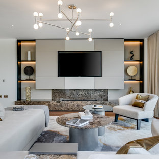 This is an example of a large contemporary living room in London with white walls, medium hardwood flooring, a wall mounted tv and brown floors.