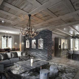 Foto di un soggiorno country di medie dimensioni e aperto con pareti grigie, pavimento in pietra calcarea, camino classico, cornice del camino in pietra e TV nascosta